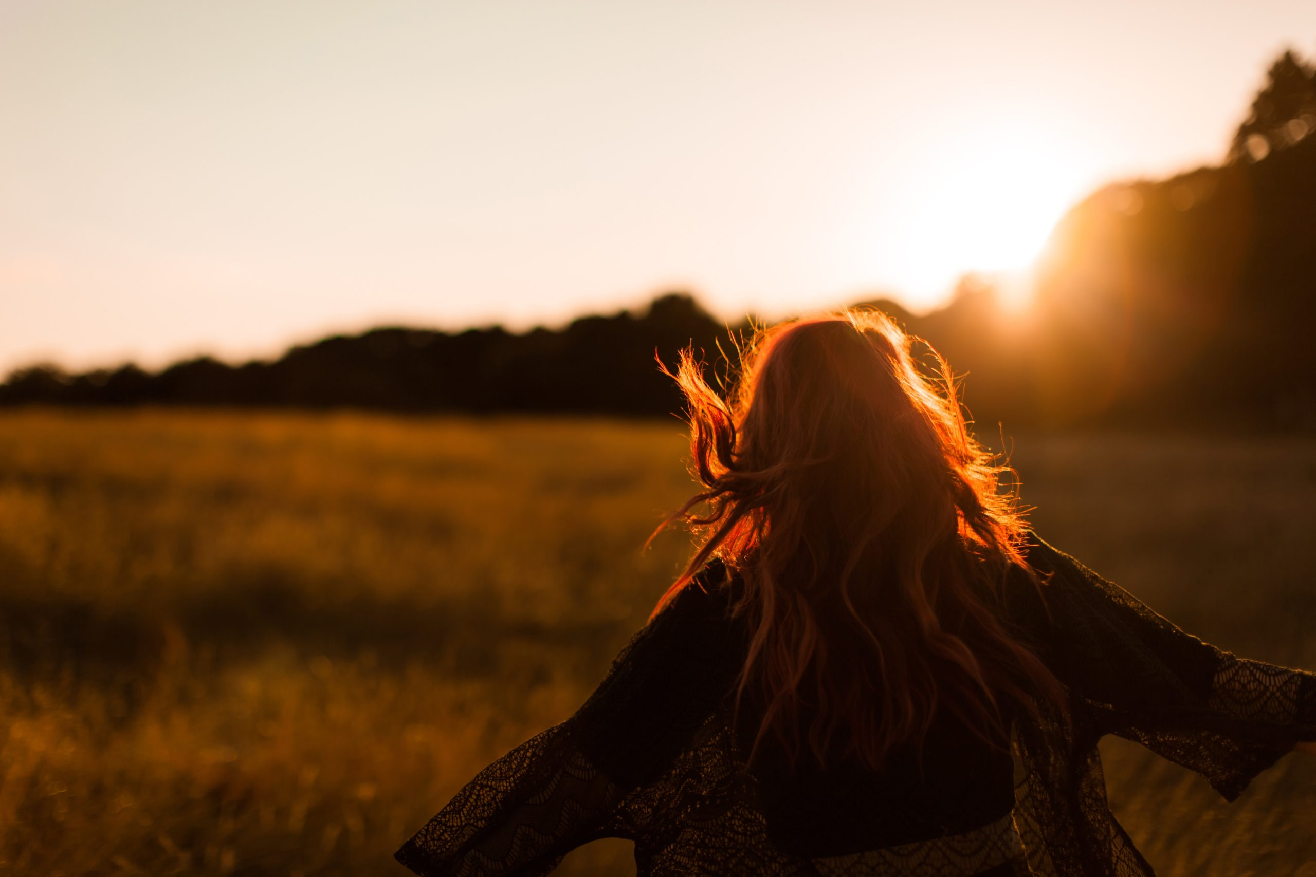 Frau steht bei Sonnenuntergang auf Feld und streckt Arme zu den Seiten
