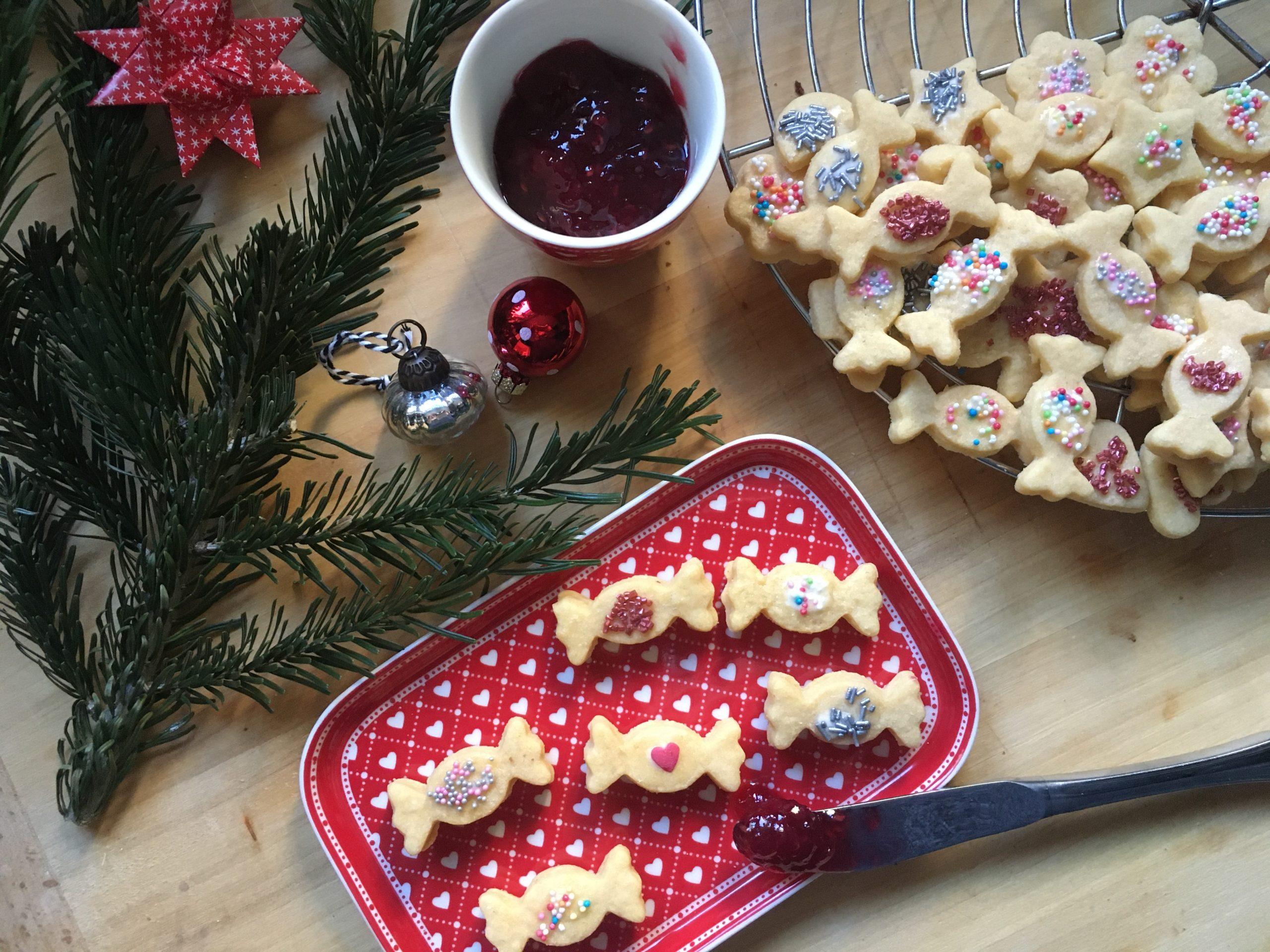 Plätzchen in Bonbonform mit weihnachtlicher Deko auf Tablett angerichtet